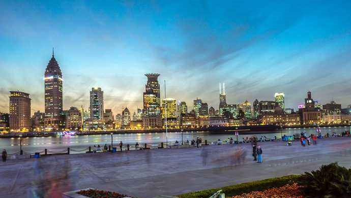 tourists walk along riverside promenade of Huangpu river in Shanghaiview on the Bund