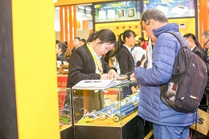 an exhibitor explains to overseas buyers the specifics of window and door drivers during exhibition