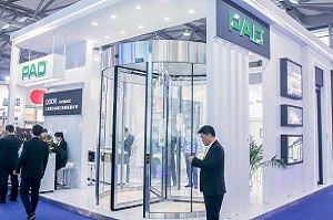 booth at the exhibition with glass automated revolvering doors  and business buyers around